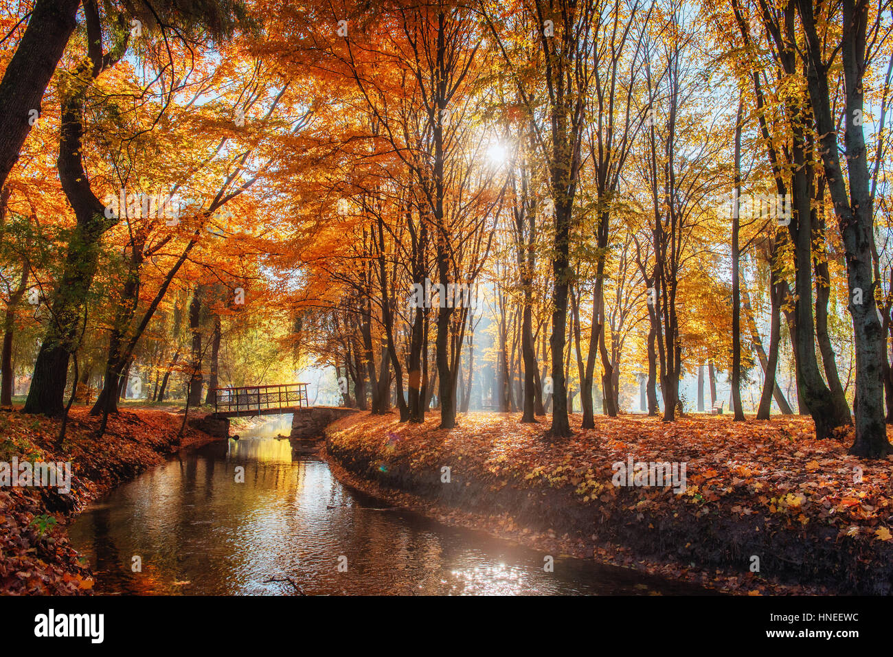 Walk way bridge over river with colorful trees - Stock Image