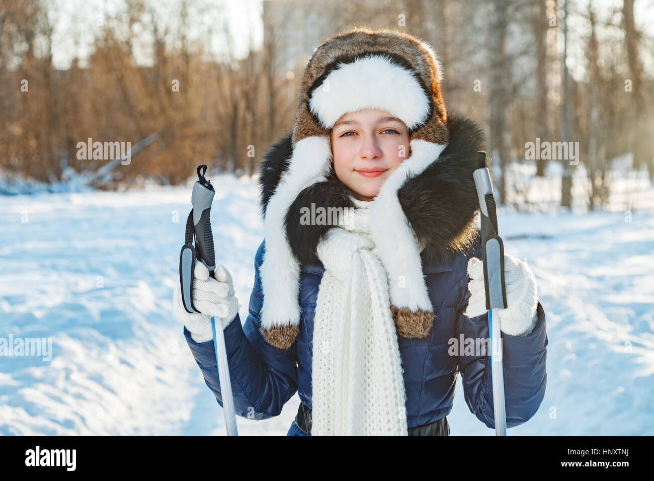 Cross-country skiing woman doing classic nordic cross country skiing in trail tracks in snow covered forest Stock Photo