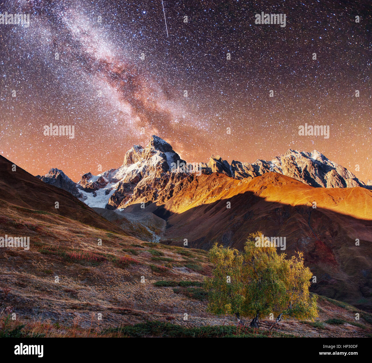Fantastic collage. Starry sky above snow-capped mountain peaks.  - Stock Image