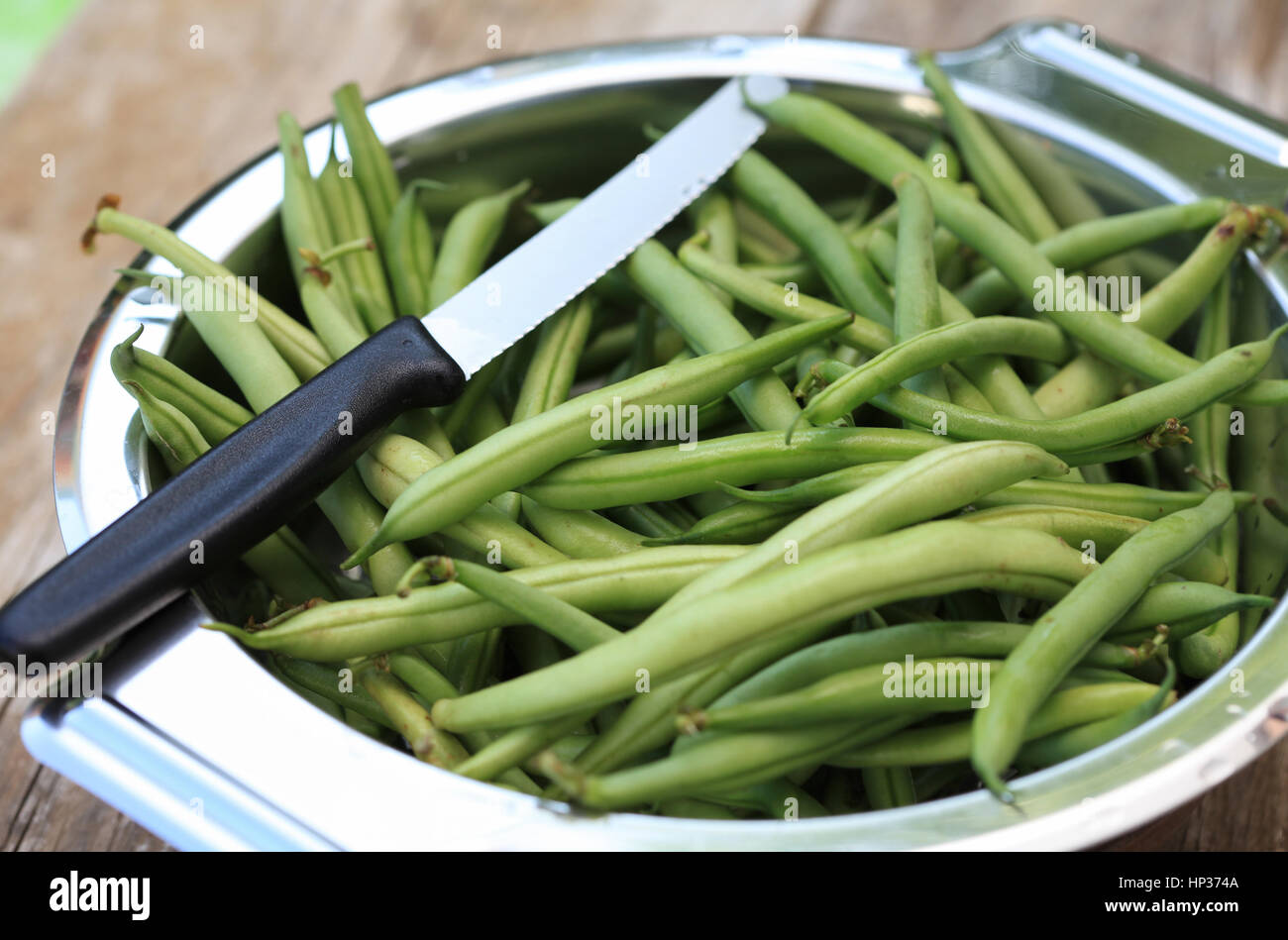 Green beans and knife in silver metal bowl - Stock Image