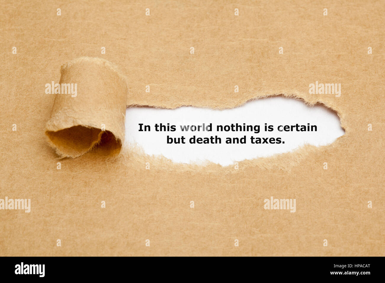Quote In this world nothing is certain but death and taxes, appearing behind ripped brown paper. - Stock Image