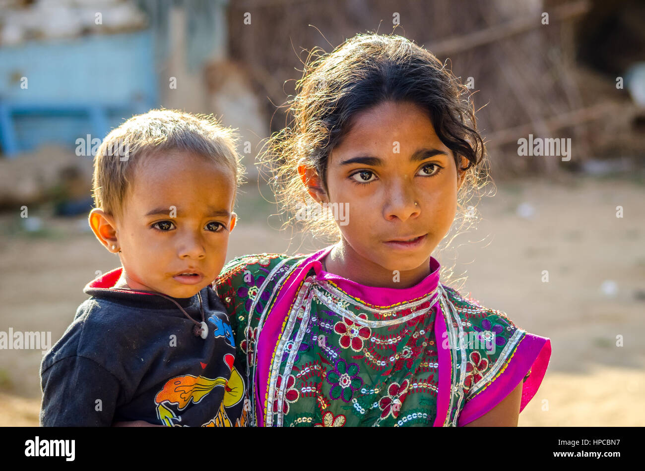 RAJASTHAN, INDIA - NOVEMBER 20, 2016: Unidentified Rajasthani poor young girl holding her brother. Stock Photo