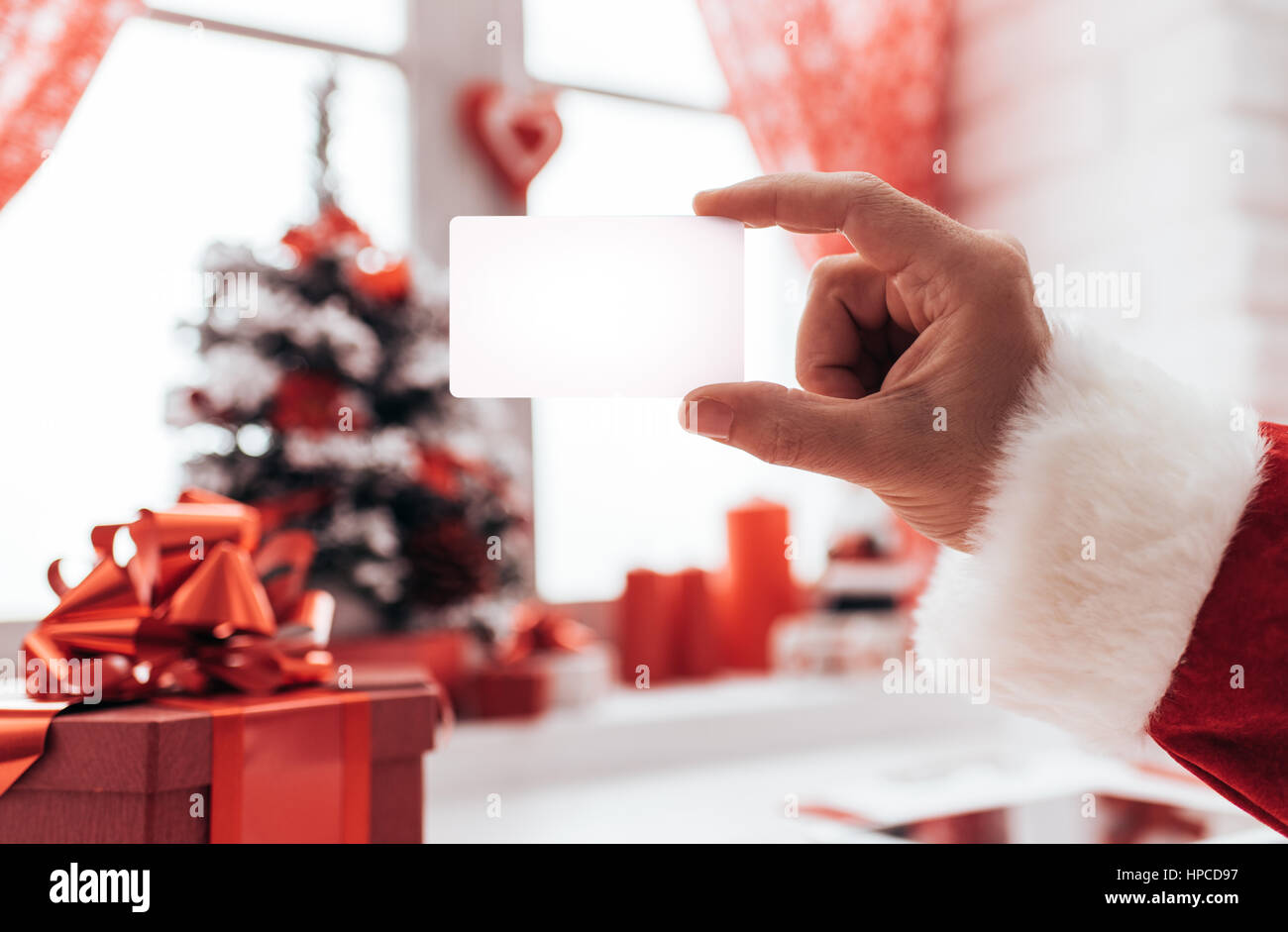 Santa claus holding a blank business card window and christmas santa claus holding a blank business card window and christmas decorations on the background colourmoves Gallery