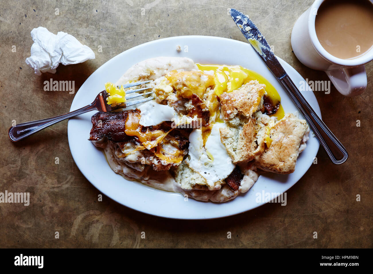 Southern Decadence - Buttermilk biscuit, chicken fried chicken, bacon, cheddar, country sausage gravy, sunny side - Stock Image