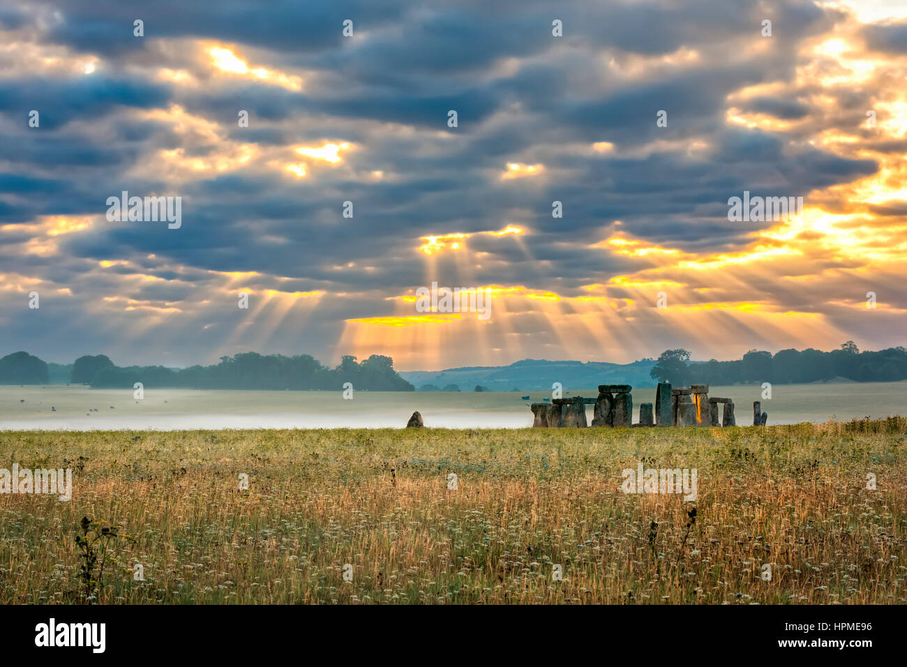 Amesbury, Wiltshire, United Kingdom - August 14, 2016: Cloudy sunrise over Stonehenge - prehistoric megalith monument Stock Photo