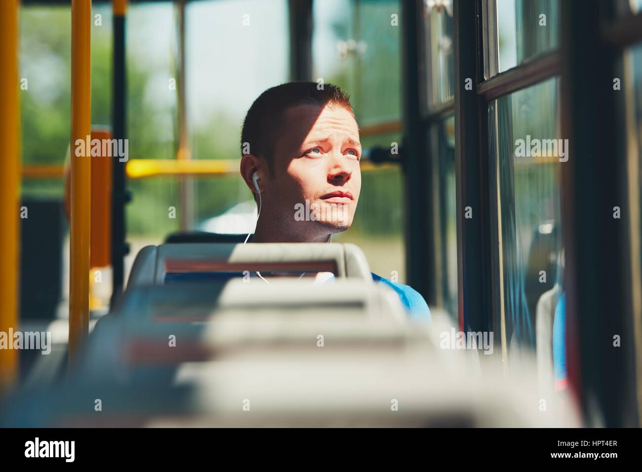 Everyday life and commuting to work by public transportation. Handsome young man is traveling by tram. - Stock Image