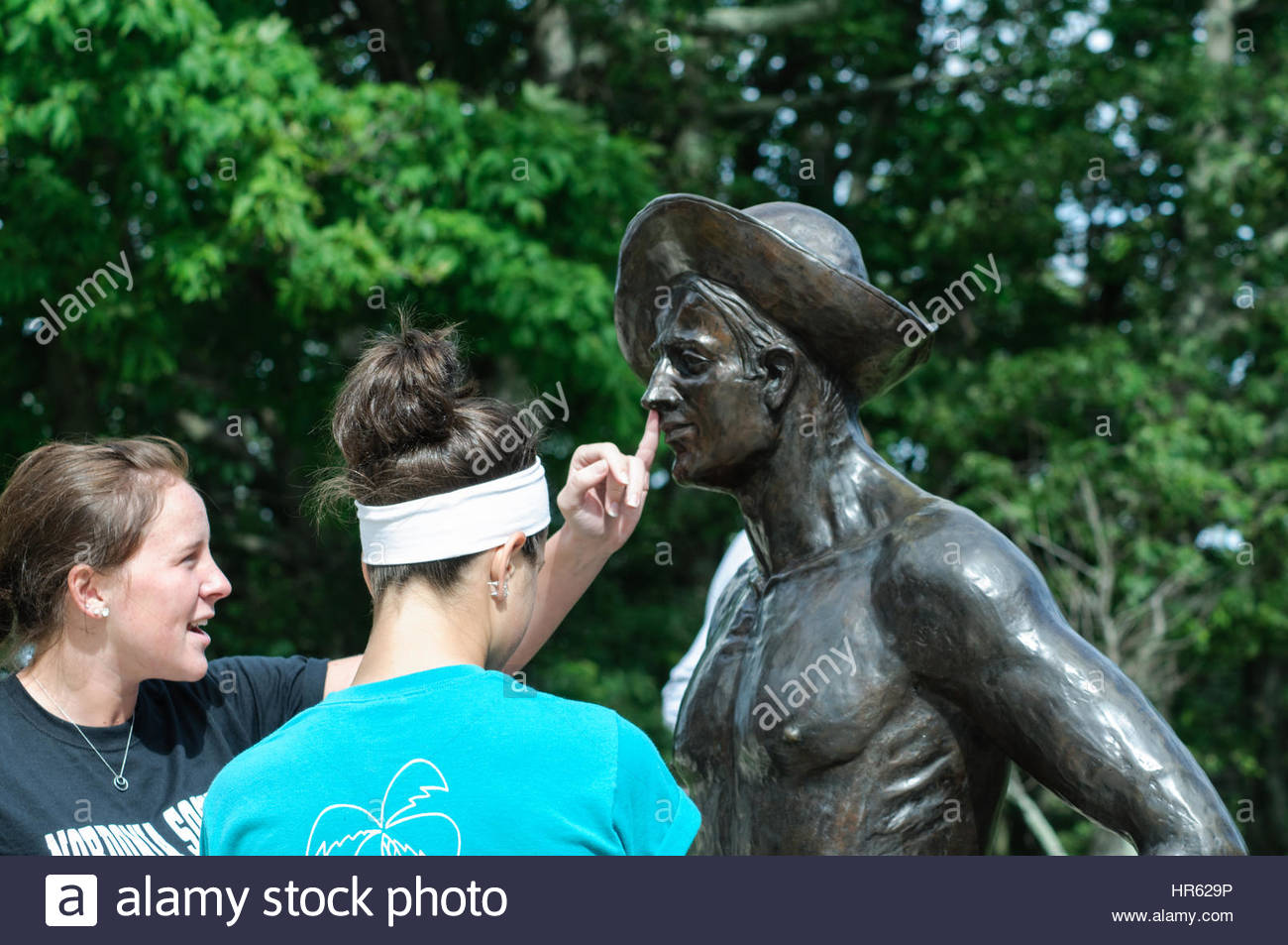 Two young girls playing with a statue of a Conservation Corp worker in the Shenandoah National Park Stock Photo