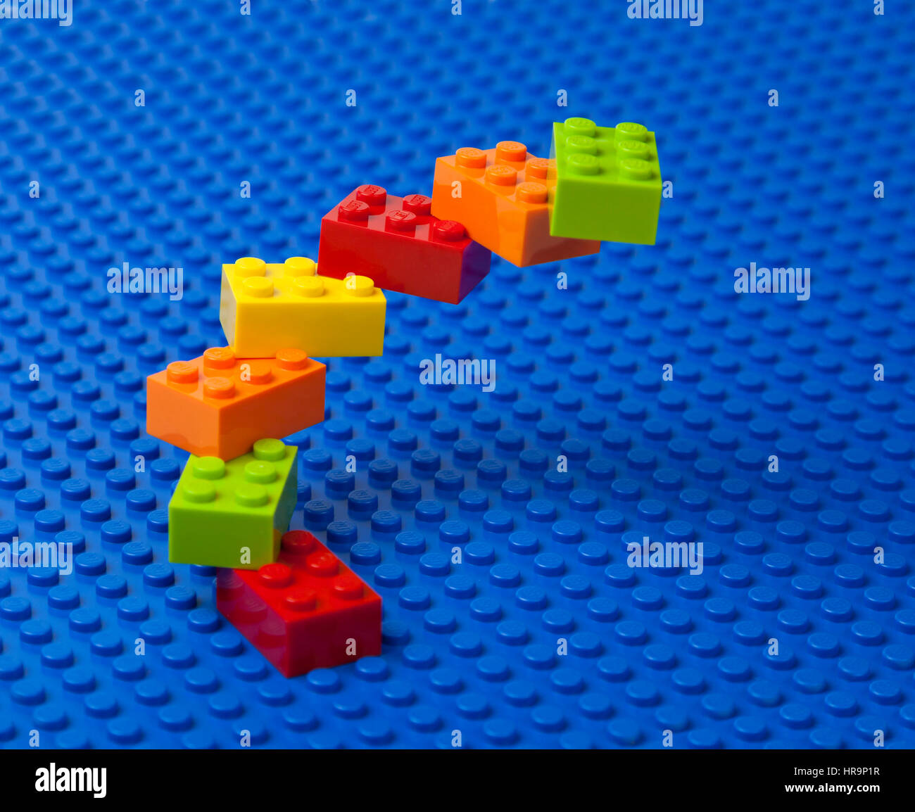 Upward spiral construction or staircase of interlocking Lego bricks on a blue Lego base plate. Stock Photo