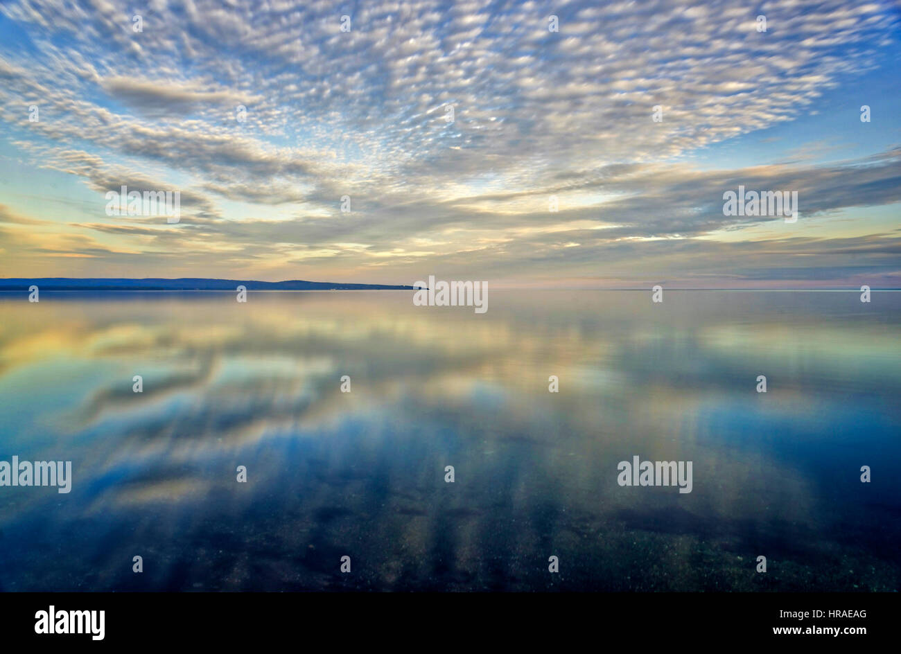 Gorgeous altocumulus clouds reflected in a nearly flat sea in Baie des Chaleurs, Gaspesie, Quebec Stock Photo