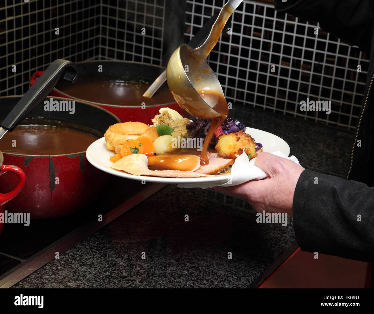 Loading a plate with vegetables and gravy at a Toby carvery pub. Stock Photo