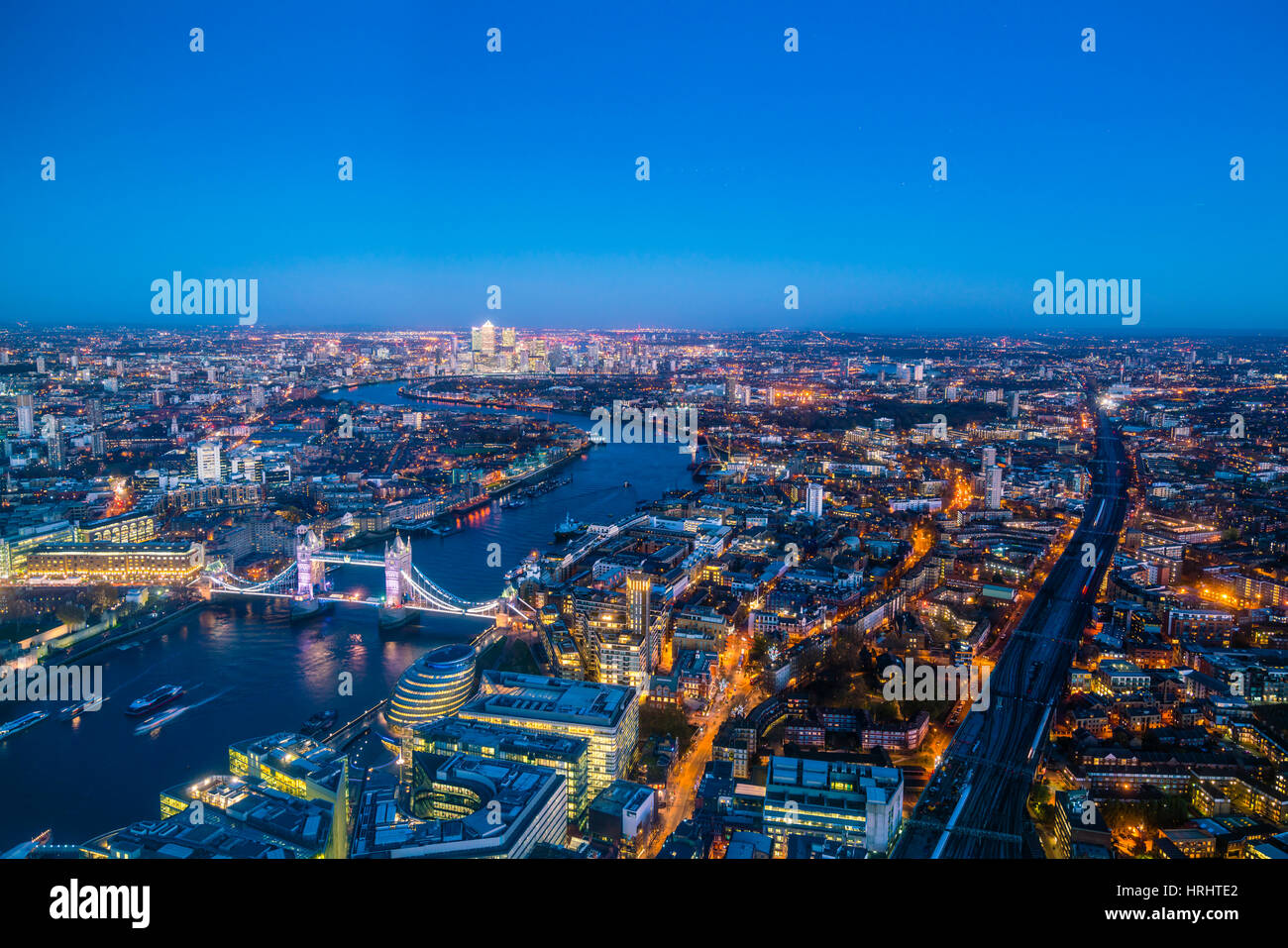 High view of London skyline at dusk along the River Thames from Tower Bridge to Canary Wharf, London, England, United - Stock Image