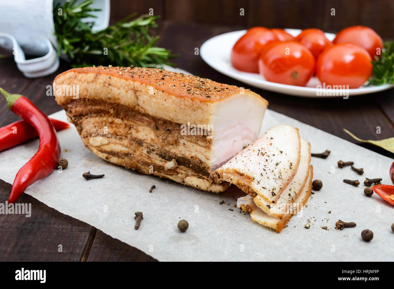 A large piece of bacon baked with spices and herbs on a paper with marinated tomatoes. A festive meal. Easter. Christmas. - Stock Image