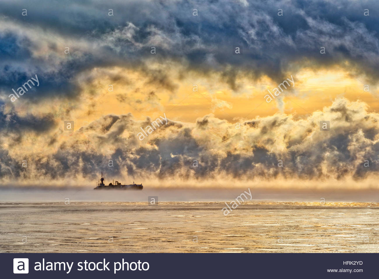 a-boat-silhouetted-against-a-dramatic-sunset-HRK2YD.jpg