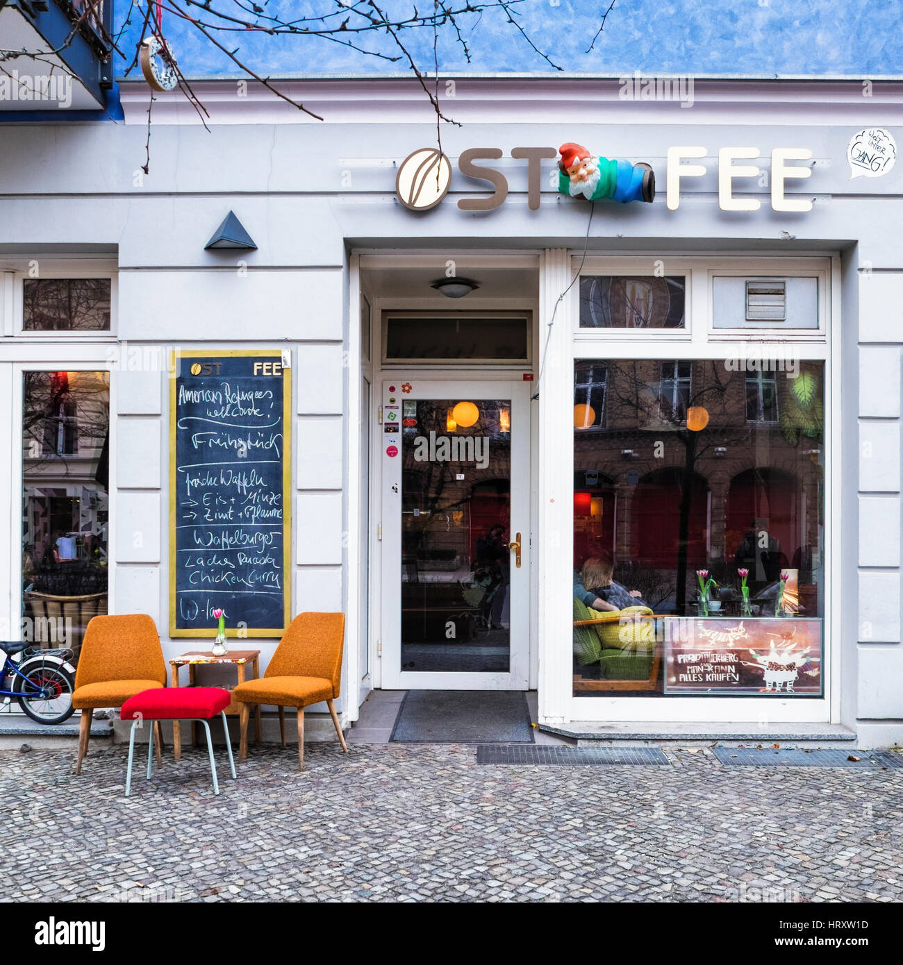 Berlin, Prenzlauer Berg., Ost Fee cafe  exterior with amusing chalkboard menu. American Refugees Welcome  - anti - Stock Image