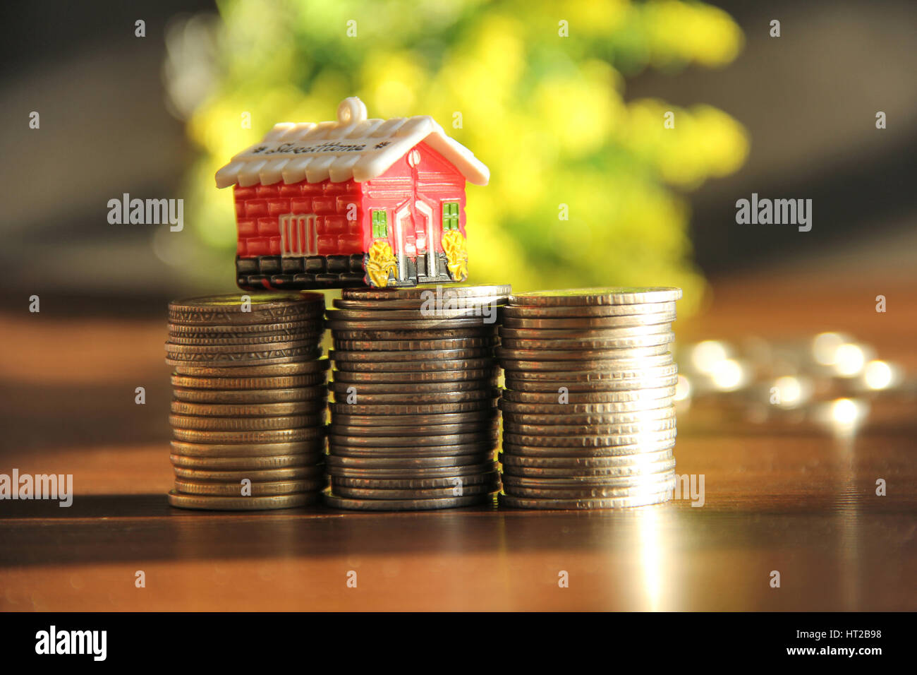 Saving money to buy house or home. Piggy bank with stack of coins - Stock Image