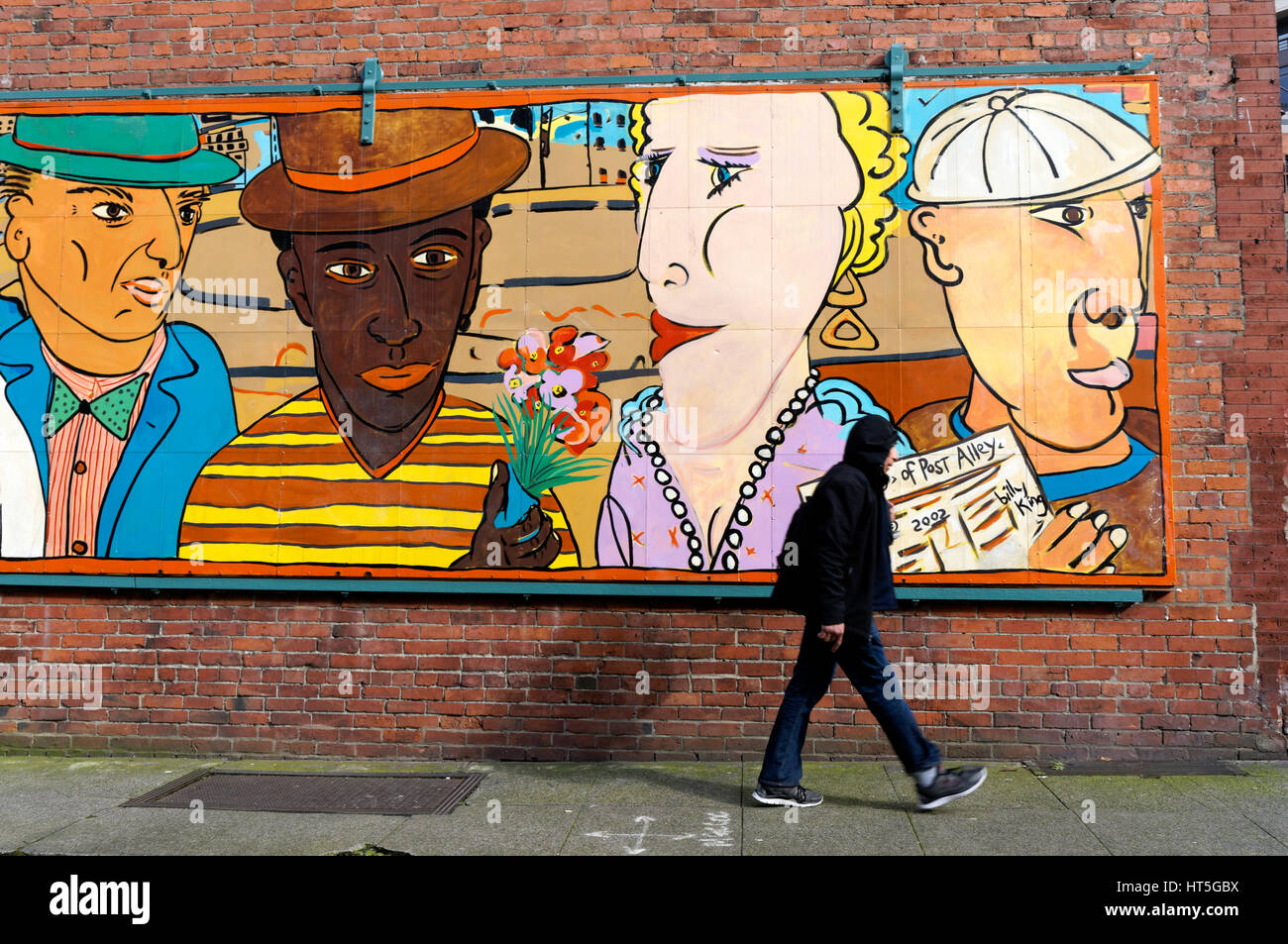 man-walking-past-a-street-mural-entitled
