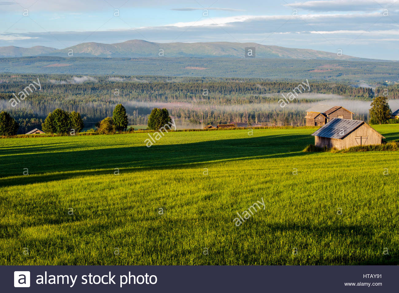 The mist lies like beautiful veils over the fields beneath the mountains. - Stock Image
