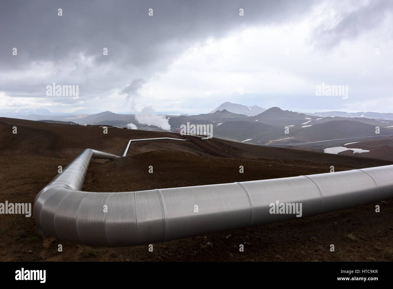 Iceland landscape with pipes in mountains. Geothermal energy in operations. - Stock Image