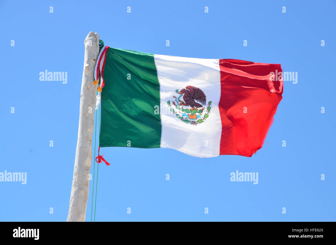 Mexican Flag Flying Against A Blue Sky In Tulum Mexico Stock Photo