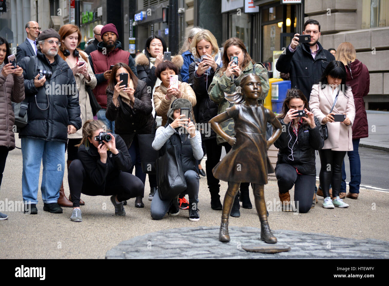 People taking pictures of 'The Fearless Girl' statue in Lower Manhattan. - Stock Image
