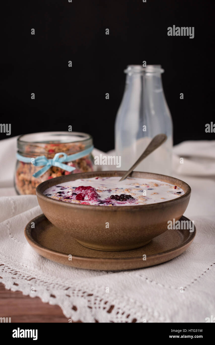 Brown bowl with milk cereal and silver spoon on right side. View from above. - Stock Image