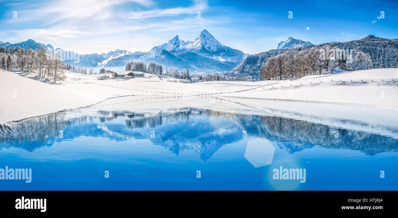 Panoramic view of beautiful white winter wonderland scenery in the Alps with snowy mountain summits reflecting in - Stock Image