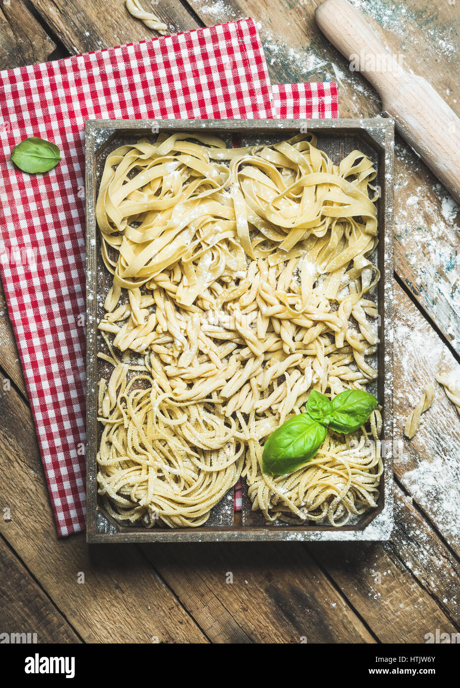 Uncooked Italian pasta in wooden tray over rustic background - Stock Image