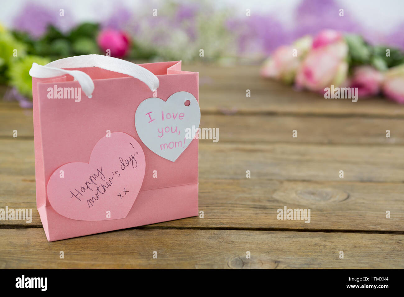 Pink gift bag with heart shape tag on wooden surface Stock Photo ...