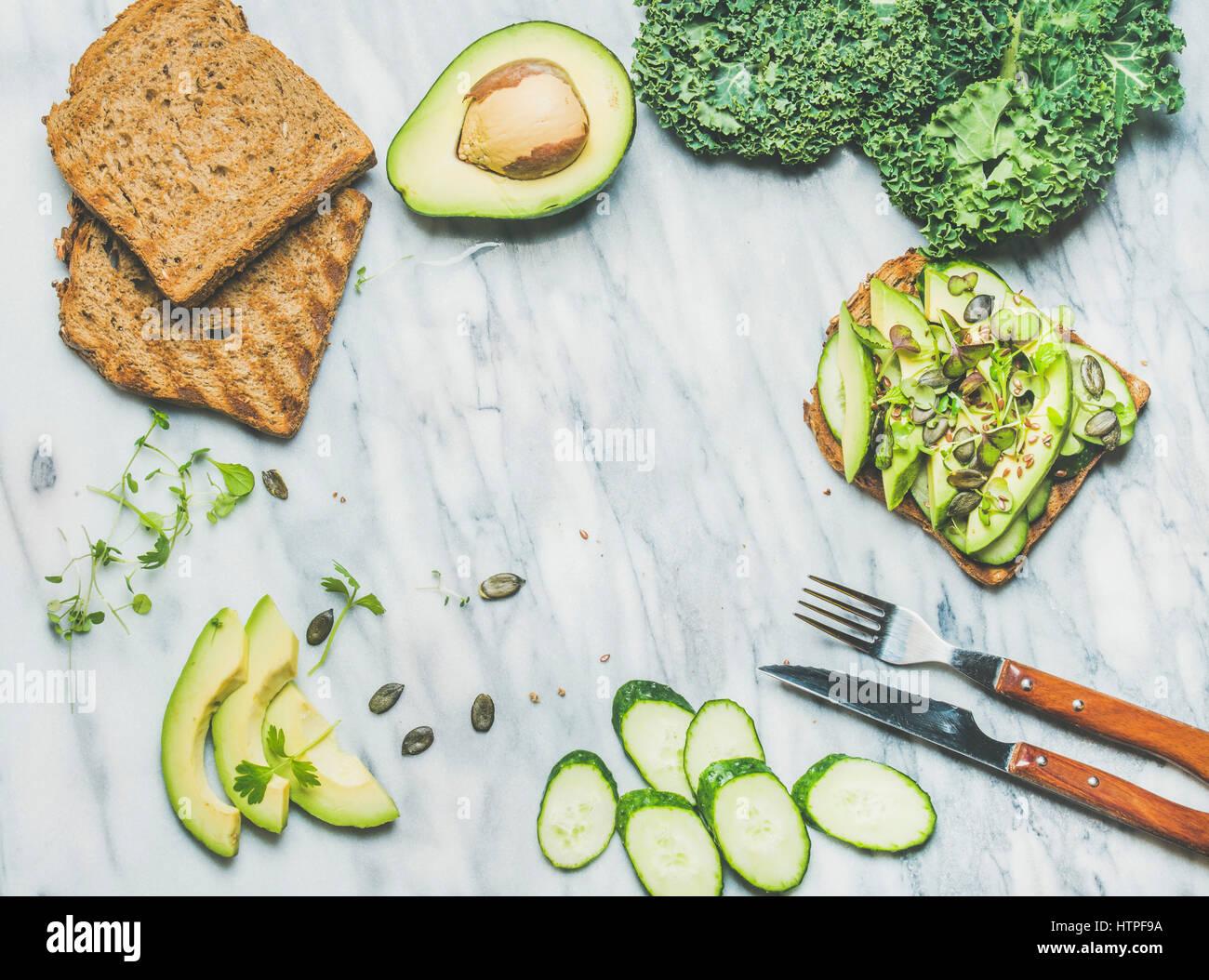 Healthy green veggie breakfast concept. Sandwich with avocado, cucumber, kale, kress sprouts, pumpkin seeds over - Stock Image