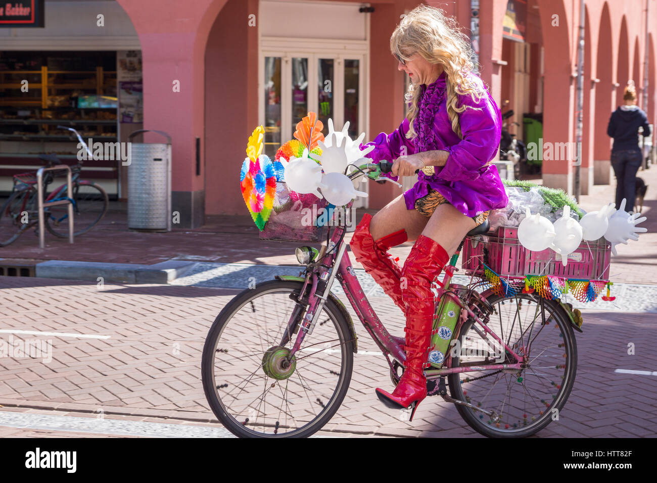 Man riding bicycle dressed up as cross-dresser ready to entertain people in Amsterdam, The Netherlands Stock Photo
