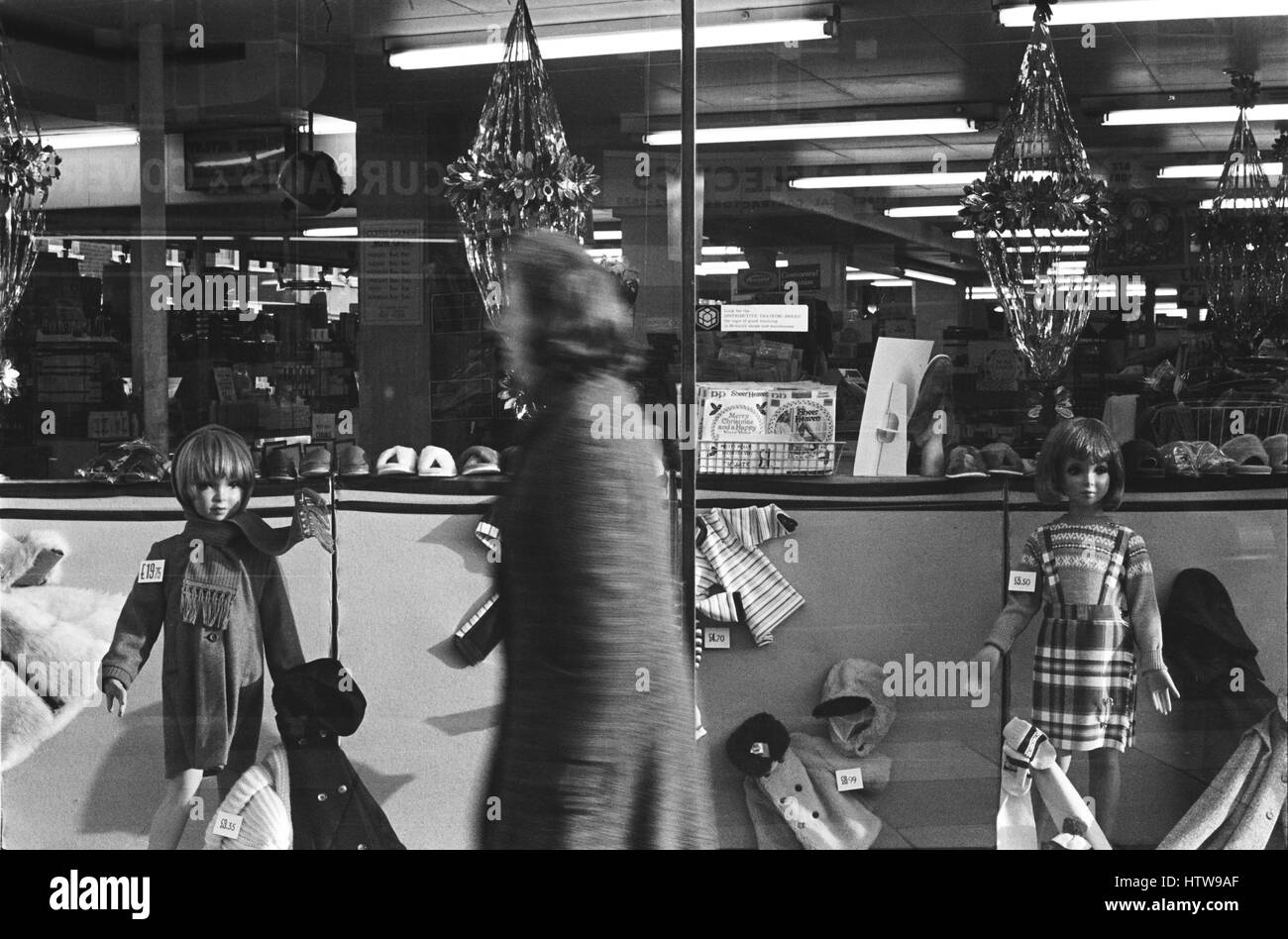 Archive image of a female shopper walking past a Christmas display of children's clothing in a department store Stock Photo
