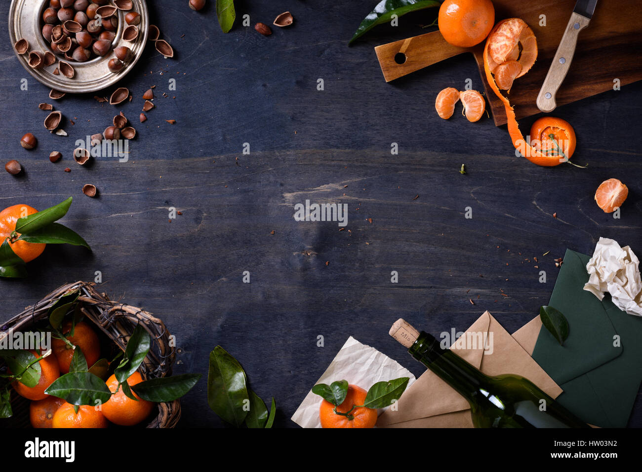 Mandarin fruits with hazelnuts and wine on wooden background. Healthy organic food frame. Top view, copy space, - Stock Image