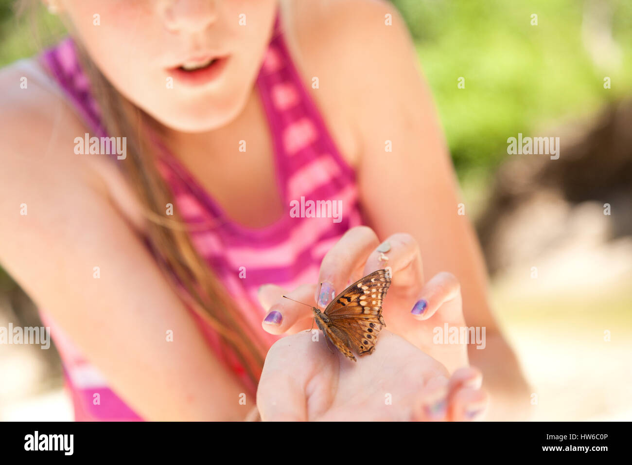 Girl with butterfly in hand - Stock Image
