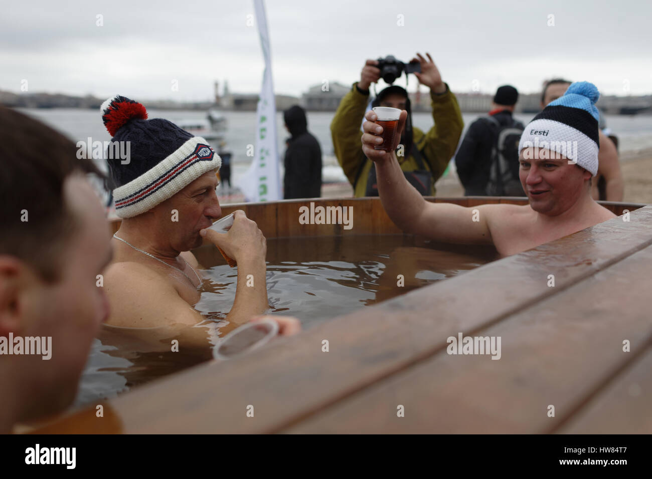 St. Petersburg, Russia, 18th March, 2017. Man drinking hot tea in the tank with warm water after a swim in river Stock Photo
