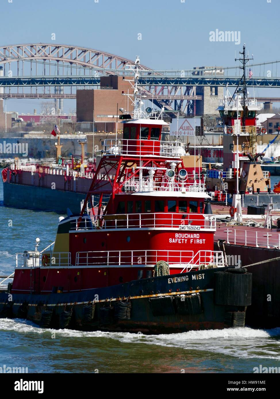 bright-red-tugboat-guides-barge-on-east-