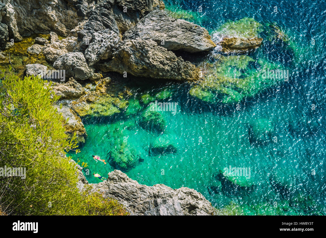 Tourists shorkling between Rocks in Azure Bay of Beautiful Paleokastritsa in Corfu Island, Greece Stock Photo