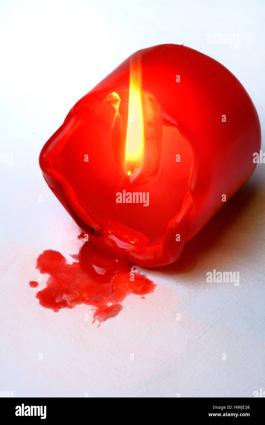 fallen over, burning candle - Stock Image