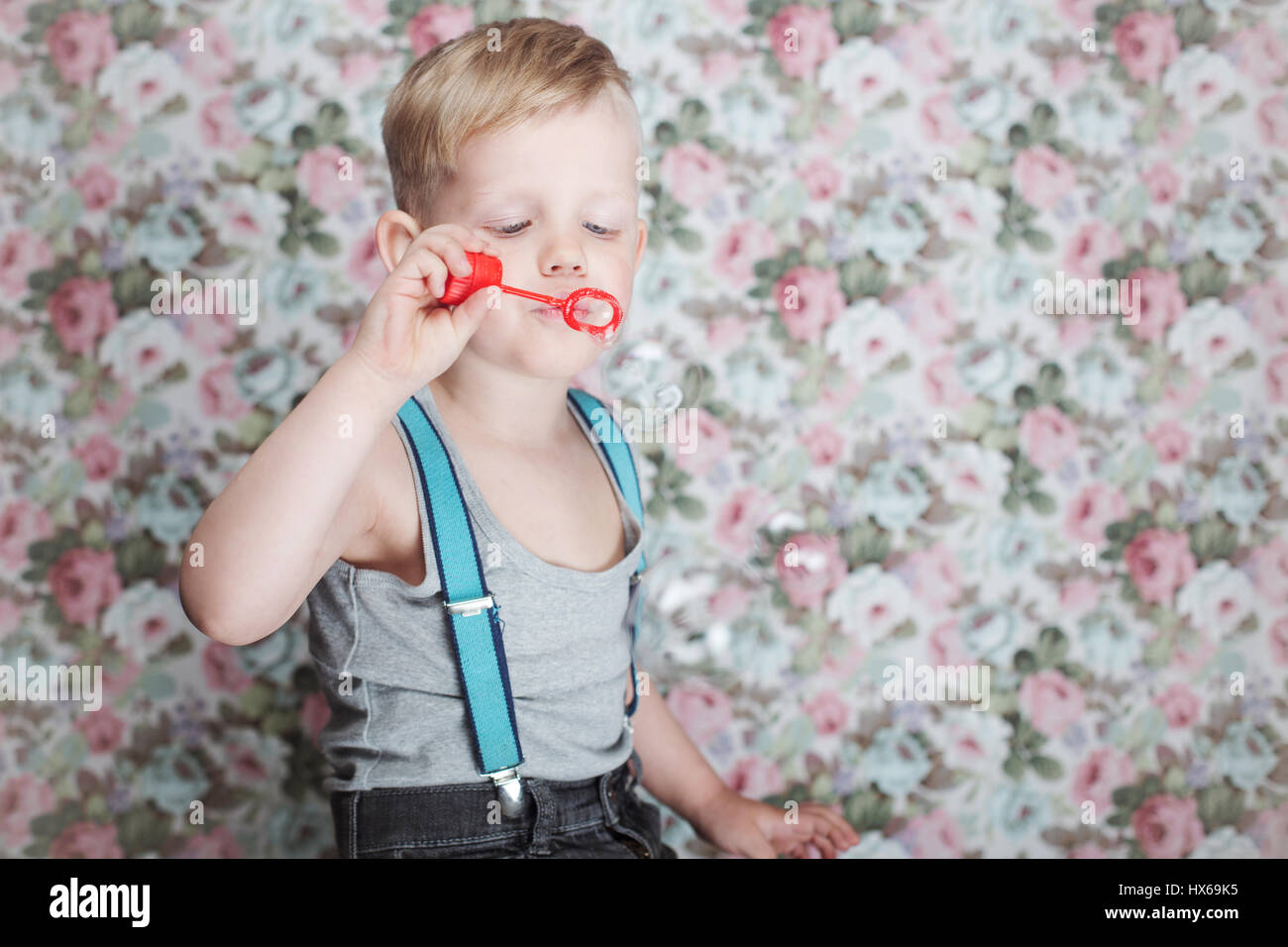 portrait of funny little boy blowing soap bubbles. background stock
