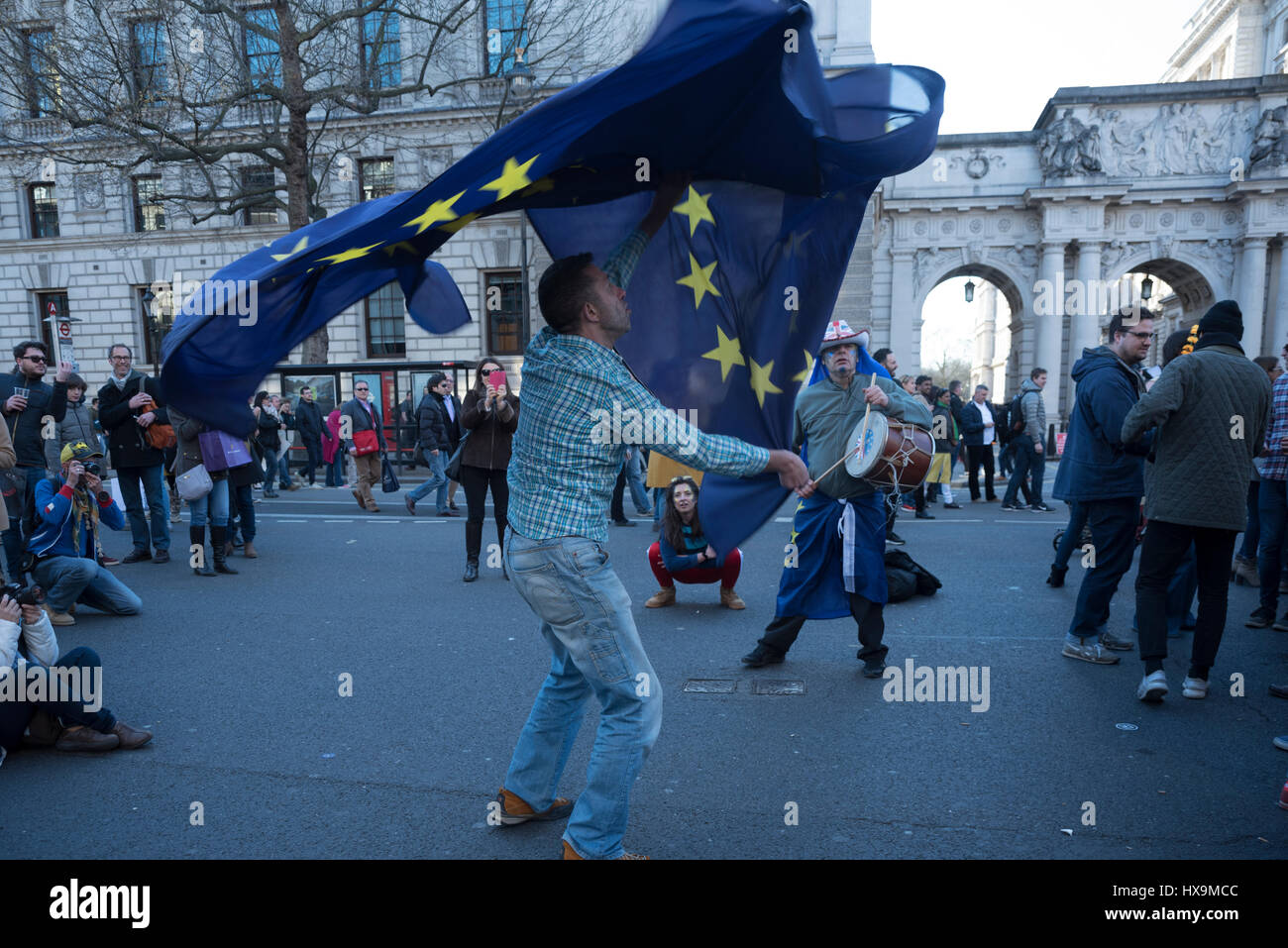 a protestor is dancing along to music using european flags to stock