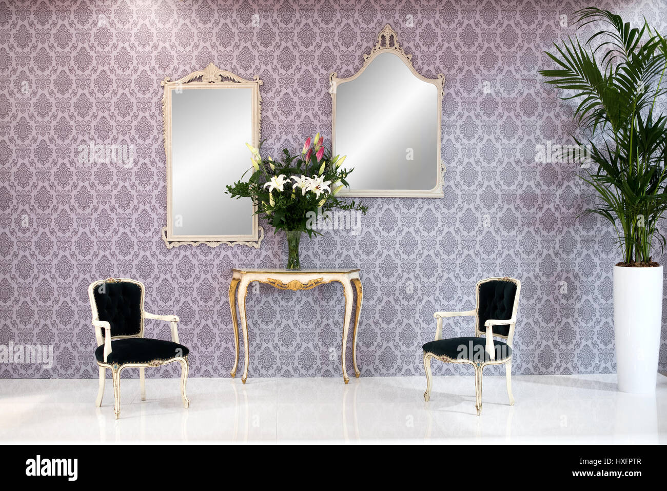 Elegant Vintage Style Living Room Interior With Patterned Arabesque  Wallpaper, Two Armchairs, Mirrors, A Large Potted Houseplant And A Console  Table W