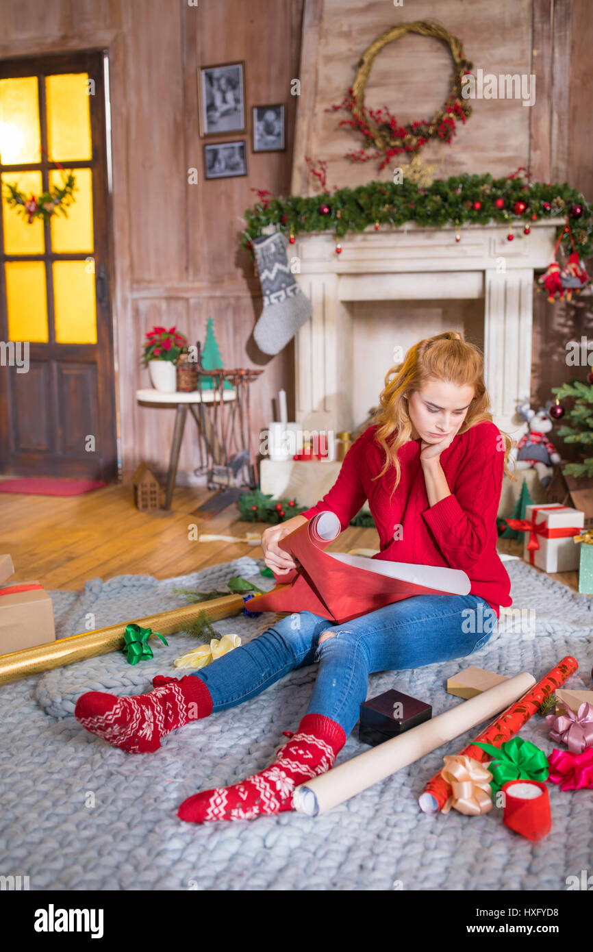 thoughtful girl sitting on grey carpet with rolls of wrapping paper and looking at christmas presents