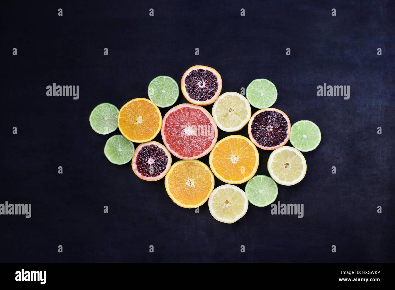 Variety of citrus fruits (orange, blood oranges, lemons, grapefruits, and limes) over a black rustic background. - Stock Image