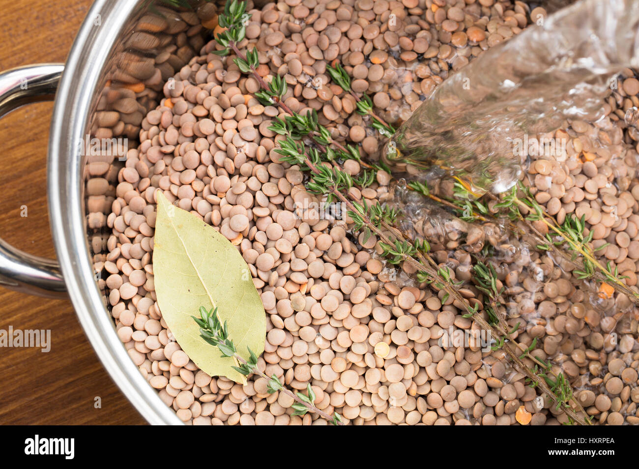 Water being poured into pot of lentils and herbs for making soup - Stock Image