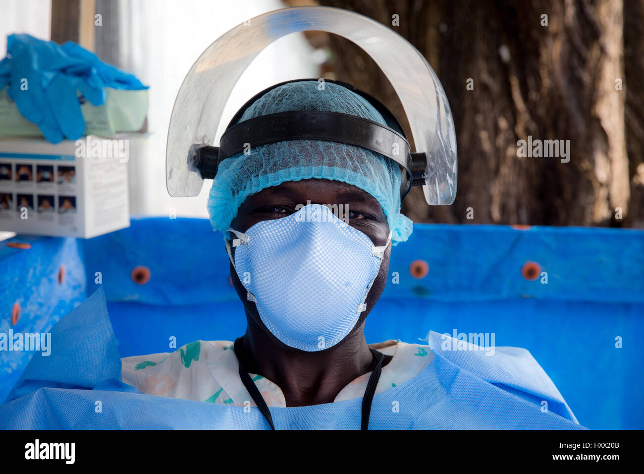 At the entrance of the ETU's everyone is prepared to encounter the sick. This man wears protective clothing just - Stock Image