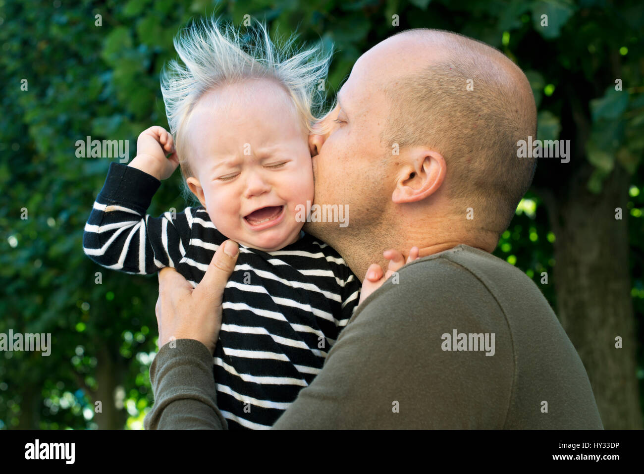 Sweden, Father kissing crying baby son (12-17 months) - Stock Image
