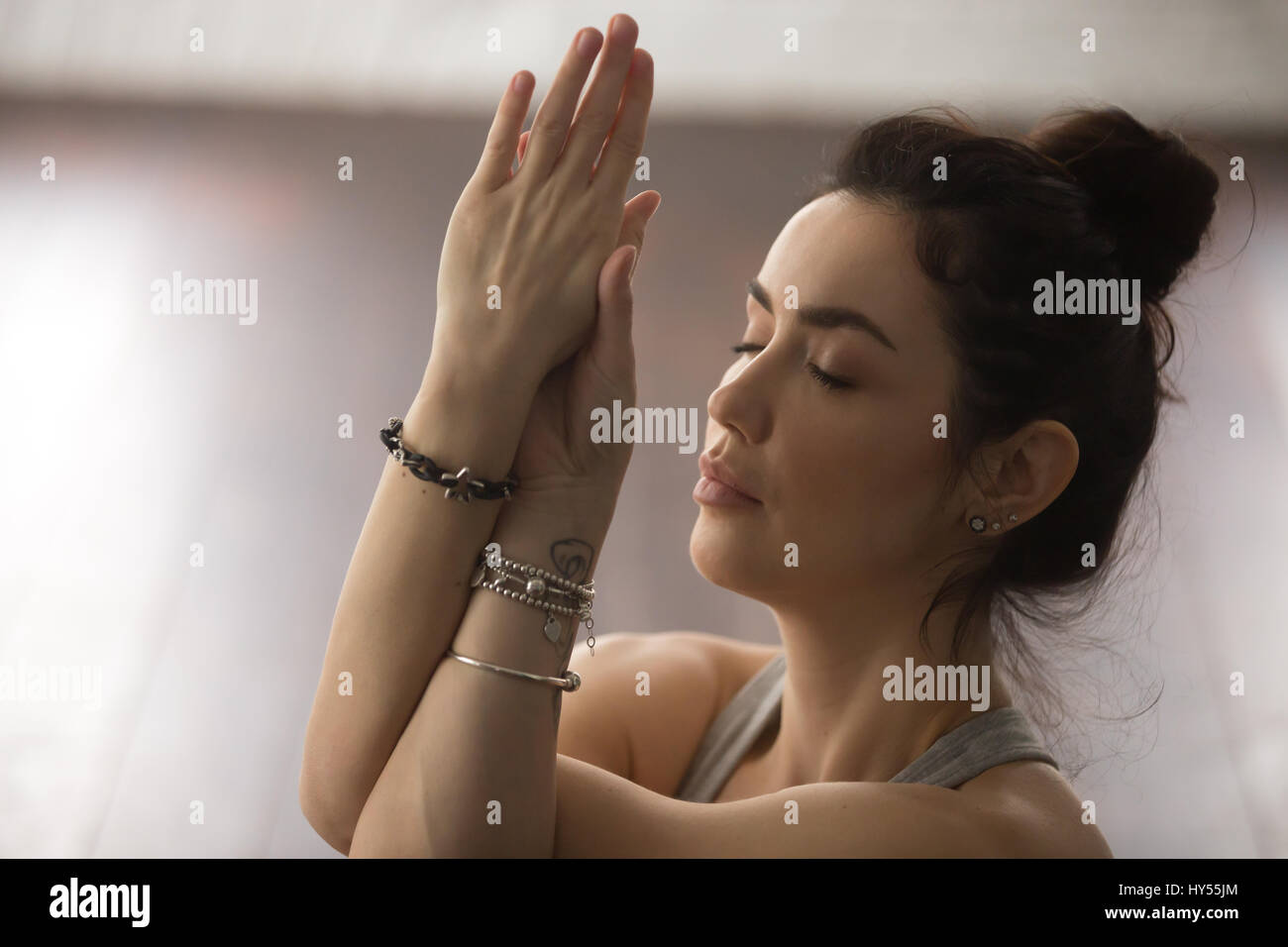 Portrait of young attractive woman meditating with closed eyes,  - Stock Image