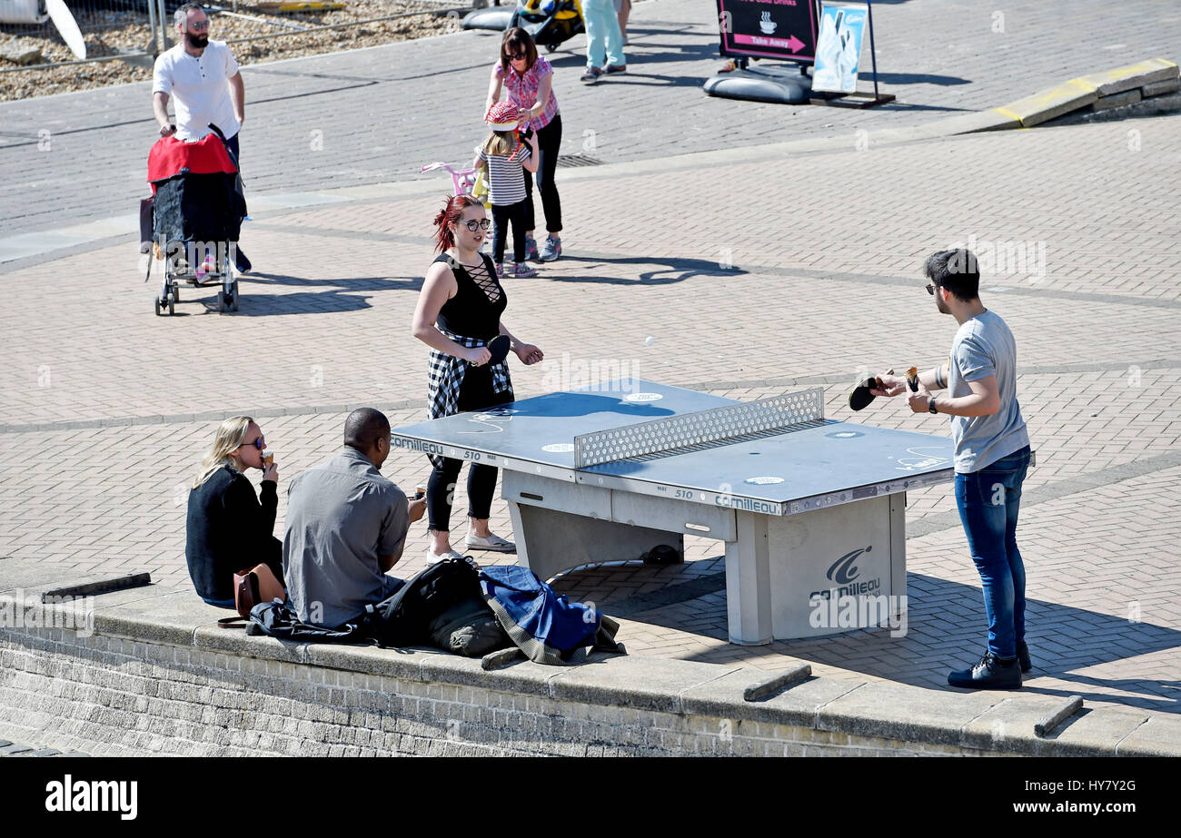 Brighton, UK. 2nd Apr, 2017. Visitors enjoy a game of table tennis in the sunshine on Brighton seafront as the warm - Stock Image