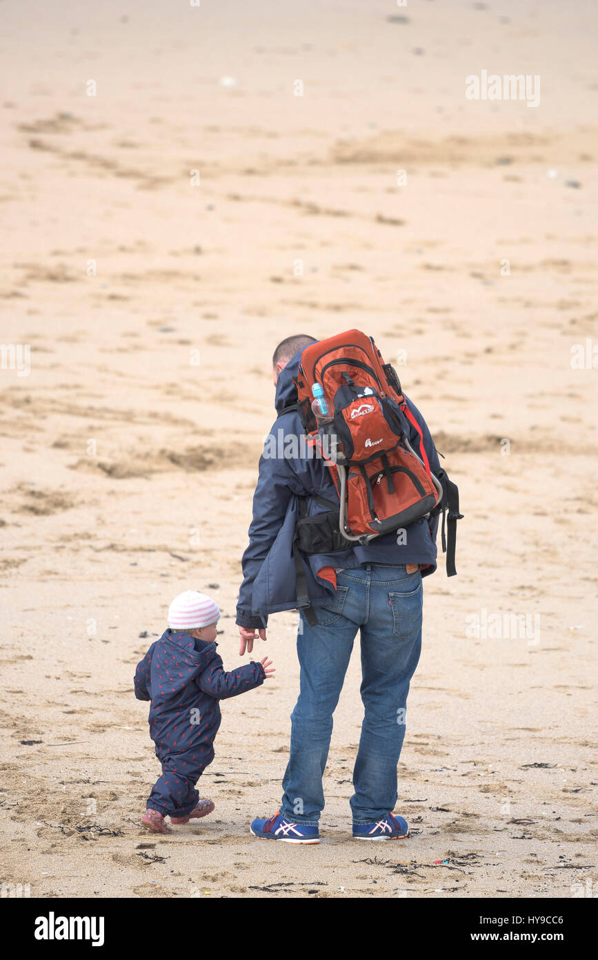 Father Child Toddler Parent Looking after a child Parenting Beach Sand Caring Together Family Activity - Stock Image