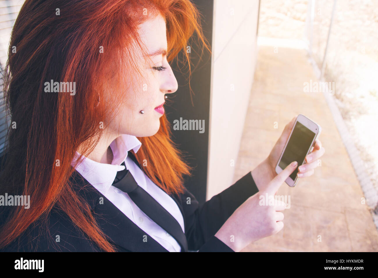 Young redhead business woman working with her smartphone - Stock Image