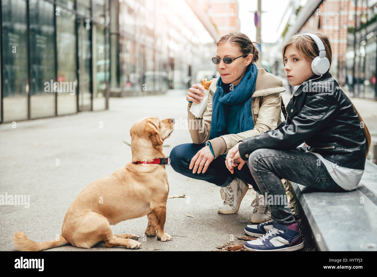 Mother eating sandwich and looking at a dog while daughter listening to music on the street - Stock Image